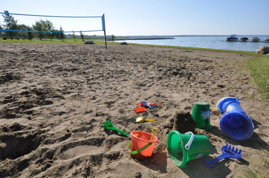 Sand toys on a beach with a beach volleyball net in the background
