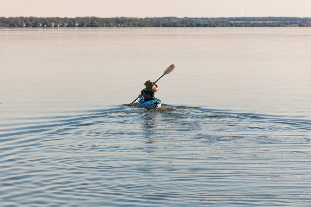 A single person is kayaking on a pristine lake